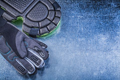 Composition of gardening safety gloves knee pads on metallic bac Stock Image