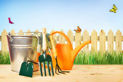 Composition with gardening tools against green grass and wooden Royalty Free Stock Photos
