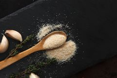 Composition of garlic powder, sprigs of thyme and cloves on black slate board. Composition of garlic powder sprinkled into wooden spoon, two sprigs of thyme and Stock Photography