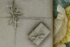 Composition of gift boxes wrapped in beige paper and bundled with ribbons. Decorated with dry leaves.  stock images