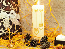 Composition with gift, candle and cones Royalty Free Stock Photo