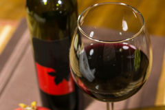 Composition of a glass and a bottle of red wine - close up Royalty Free Stock Image
