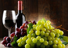 Composition with glass, bottle of red wine and fresh grapes. stock photo