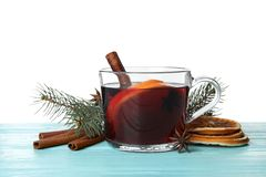 Composition with glass cup of mulled wine, cinnamon, orange and fir branch on table. Against white background royalty free stock photo