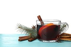 Composition with glass cup of mulled wine, cinnamon, orange and fir branch on table against white background. Space for text royalty free stock photos