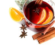 Composition with glass cup of mulled wine, cinnamon, orange and fir branch on white. Background royalty free stock photography