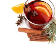 Composition with glass cup of mulled wine, cinnamon, orange and fir branch. On white background royalty free stock photos