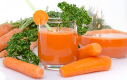 Composition with a glass and a jug of carrot juice, fresh carrot Stock Photos