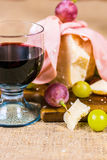 Composition of glass of red wine, grape, cheese and salami on a wooden board and canvas Stock Photography