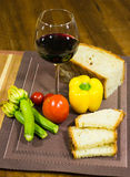 Composition of a glass of red wine, home made bread, pepperoni, courgettes and red tomatoes on a table Stock Images
