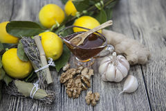 The composition of glass vase with floral honey and wooden spoon with lemon provencal herbs walnuts, garlic  and ginger on a woode Stock Photo