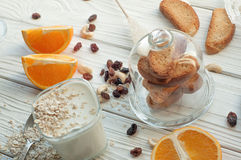 A composition with a glass of youghurt, a fresh orange cut up into several pieces, cereal, nuts and raisins Stock Photos