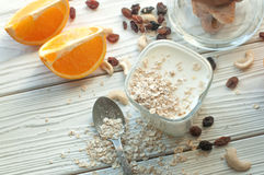A composition with a glass of youghurt, a fresh orange cut up into several pieces, cereal, nuts and raisins Royalty Free Stock Image