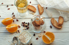 A composition with a glass of youghurt, a fresh orange cut up into several pieces, cereal, nuts and raisins Stock Photo
