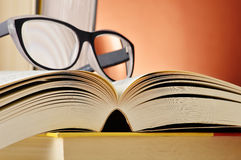 Composition with glasses and books on the table Stock Images