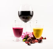 Composition of a glasses with cocktails - black, pink, yellow and flowers on a white background Royalty Free Stock Photo