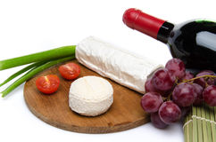 Composition of goat cheese on a wooden cutting board Royalty Free Stock Photo
