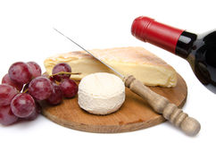 Composition of goat and cow cheese on a wooden cutting board Royalty Free Stock Images