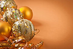 Composition of golden christmas balls on light brown background Royalty Free Stock Image
