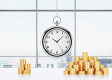 A composition of golden coins and hanging on the chain pocket watch. New York panoramic office on background. A concept of time is Stock Photo