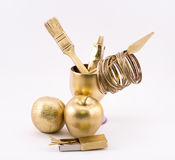 Composition of golden objects - apple, orange, glass, brush, matches, rings and spatula Royalty Free Stock Photography