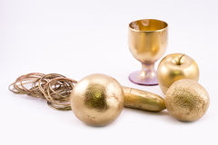 Composition of golden objects - apple, oranges, glass, rings Stock Photo