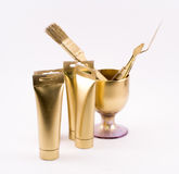 Composition of golden objects - paint tubes, brush, spatula, glass Royalty Free Stock Photo