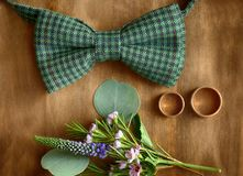 Composition of golden wedding rings, flowers. And bow tie on wooden background Stock Photography