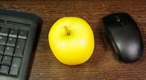 Composition with green apple, mouse and keyboard. Laying on wooden desk. Selective focus on apple royalty free stock photography