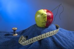 Composition: green-red apple with the needle and thread on a blue towel. Near it blue coil of thread and centimeter for sewing. Composition: green-red apple with royalty free stock photography