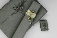 Composition of grey gift boxes wrapped in paper and bundled with different ribbons on grey background.  royalty free stock images