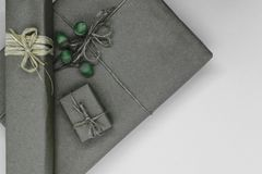 Composition of grey gift boxes wrapped in paper and bundled with different ribbons and young oak acorns on it.  stock image