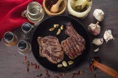Composition grillée en bifteck d'oeil de nervure sur la casserole de fer de gril sur le fond en bois Photos libres de droits