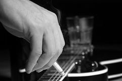 Composition of guitar and man's hand with cigarette smoking Royalty Free Stock Photos