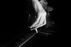 Composition of guitar and man's hand with cigarette smoking Royalty Free Stock Images