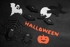 Composition of Halloween with paper bats spiders and ghosts with an inscription on a black background royalty free stock photo