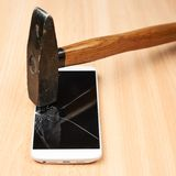 Composition of hammer and a broken phone Stock Images