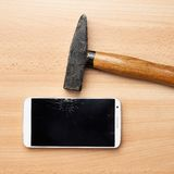 Composition of hammer and a broken phone Royalty Free Stock Images