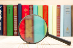 Composition with hardback books and magnifying glass on the table. Back to school, copy space. Education background. Stock Photography