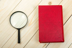 Composition with hardback books and magnifying glass on the table. Back to school, copy space. Education background. Stock Photo