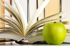 Composition with hardcover books and apple in the library Stock Photo