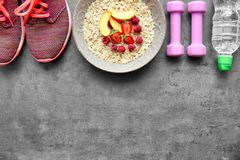 Composition with healthy oatmeal and sport equipment. On grey background Stock Photo