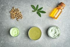 Composition with hemp cosmetic products. And natural ingredients on grey background Stock Photos