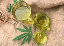 Composition with hemp oil in jugs. On sackcloth stock photography