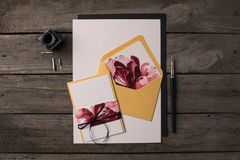 Holiday invitations with floral illustrations. Composition of holiday invitations with floral illustrations on rustic wooden table Royalty Free Stock Photo