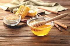 Composition with honey and cinnamon. On wooden table royalty free stock image