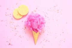 Composition of ice cream cone with pink wisp of bast on a light pink background. Bathroom cosmetic accessories. Flat Lay. Top View. Sea salt stock photo