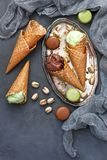 Variety of ice cream  in cones with chocolate and pistachio. Composition with ice cream  and cookies on concrete background. Top view with copy space Royalty Free Stock Image