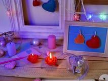 Composition intérieure de fête saisonnière des bougies allumées, décor, cadres en bois, lampes décoratives, coeurs de feutre, pap photos libres de droits