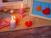 Composition intérieure de fête saisonnière des bougies allumées, décor, cadres en bois, lampes décoratives, coeurs de feutre, pap image libre de droits